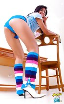 Bending over chair looking over her shoulder wearing blue shorts in high heels