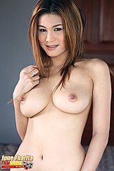 June Tharita With Her Arm Raised Over Her Bare Breasts Tendrils Of Her Long Hair Touching Her Tits