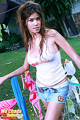 Standing In Garden Beside Washing Line Long Hair Straggling Over Her Shoulders Wearing Tshirt In Denim Shorts