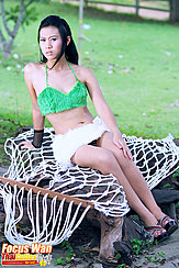 Seated On White Netting Wearing Green Top In Short Skirt
